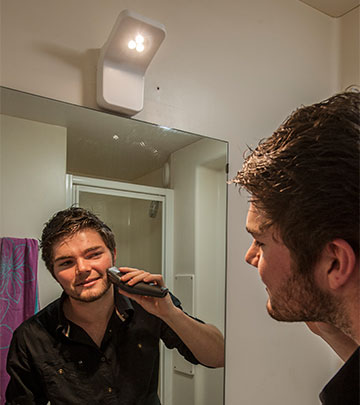 Guy shaving his beard in front of the mirror